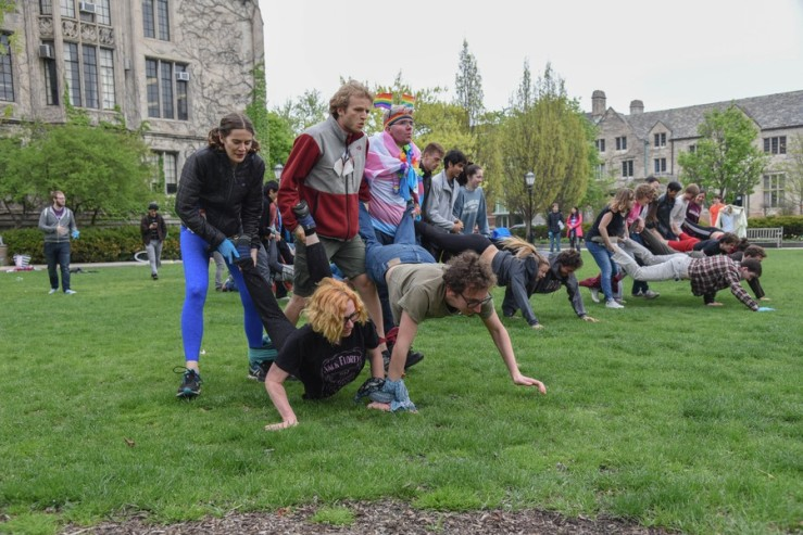 Many people on the Quad of UChicago in teams of five. On each team, three people hold the legs of two people in a wheelbarrow position. Front and center is a team made up of L. A. Lanquist and a group named Cactus Emoji.