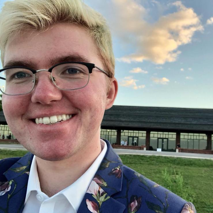 Leland Ashford Lanquist smiling, in a floral dark blue suit and a crisp white shirt, with square glasses, bleached hair, and pink skin. In the background is a lawn in front of a long building and a pretty sky with a few sunlit clouds.