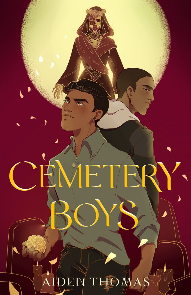 """The cover of Cemetery Boys, with Yadriel looking up in the foreground holding a marigold. He is wearing a button down and a pendant. Behind him, Julian stands facing away, wearing a hoodie and looking behind him at Julian. Behind the two are tombstones and candles. Marigold petals swirl around the two and back towards the moon which takes up the upper third of the cover. Those petals, however, do not originate from the moon, but from Lady Death, who stands resplendent in red with her own crown of marigolds, looking down at the two lead characters. In large gold text covering Yadriel's torso are the words """"CEMETERY BOYS"""". Below that, at the bottom of the cover in smaller, lighter text, are the words """"AIDEN THOMAS""""."""